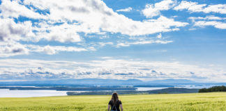 Katarina på ett fält framför Storsjön och Oviksfjällen