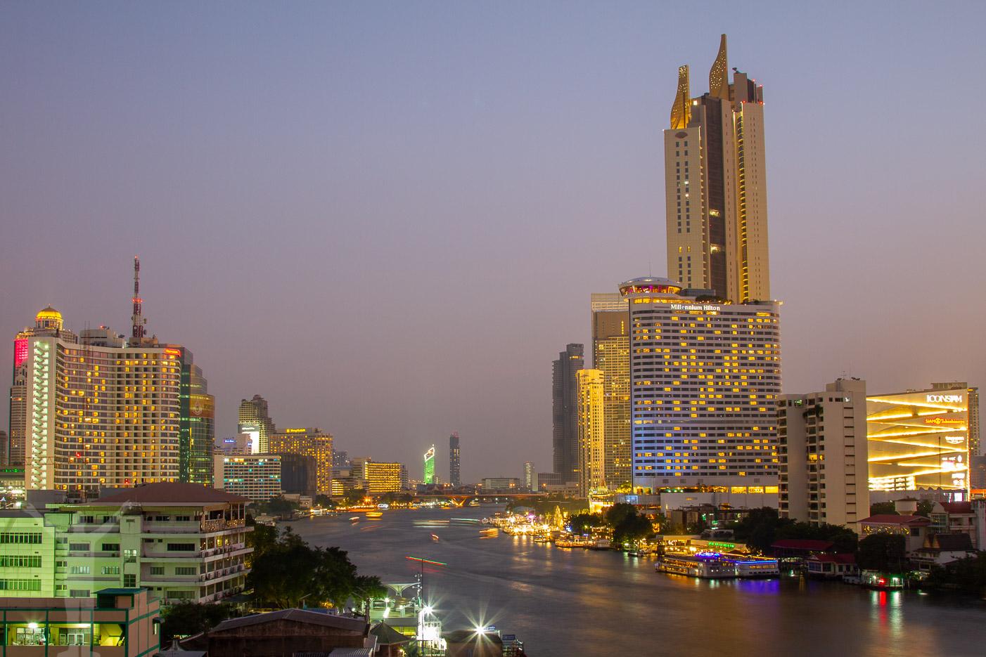 Kvällsfoto från en takbar och full trafik på Chao Phraya.