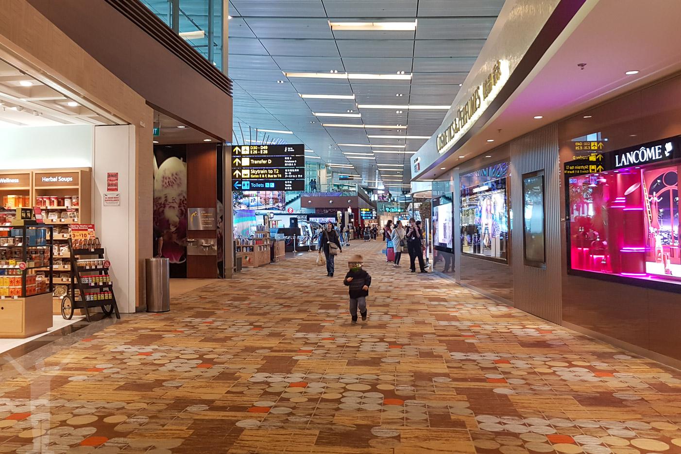 Promenadstråk med affärer i Terminal 1 på Changi.