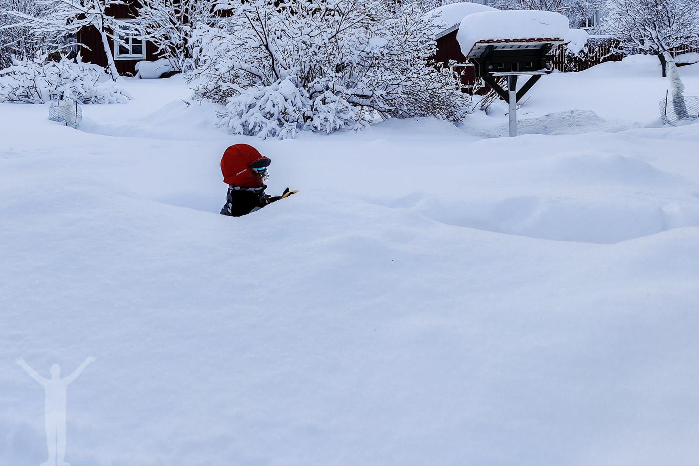 Ett barn som knappt syns bakom snön